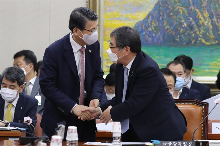 Financial Services Commission (FSC) Chairman Eun Sung-soo, left, shakes hands with Financial Supervisory Service (FSS) Governor Yoon Suk-heun at a National Assembly committee meeting in Seoul, Wednesday. At the meeting, the two financial authority chiefs vowed to take stern measures to prevent the creation of new financial scheme products by strengthening supervision and enhancing regulations. / Yonhap