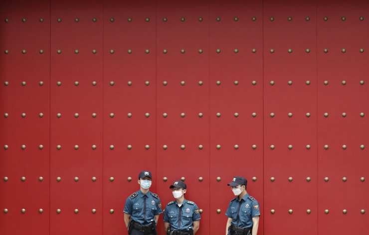 Police officers wearing face masks to help protect against the spread of the new coronavirus stand guard in downtown Seoul, July 7, 2020. AP