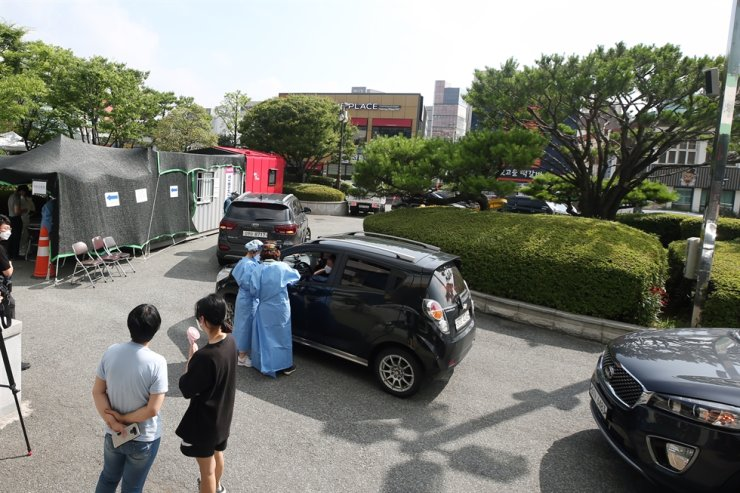 Medical staff take a sample from a citizen at a drive-thru COVID-19 testing site in Gwangju, Wednesday. The southwestern city has reported more than 80 virus patients in about 10 days. / Yonhap