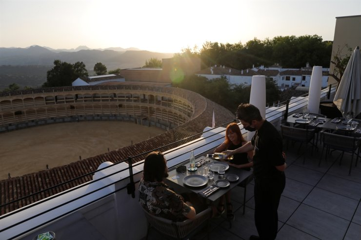 A waiter wears a protective face mask as he serves wine to Australian tourists after the easing of restrictions imposed to control the spread of COVID-19, at the terrace restaurant at the Catalonia Ronda hotel, in front of a bullring at sunset in downtown Ronda, southern Spain, June 29. Reuters