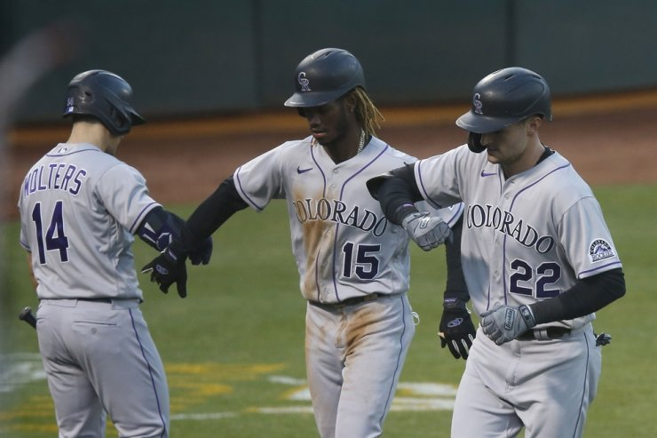 Sam Hilliard, right, of the Colorado Rockies celebrates with Raimel Tapia, center, and Tony Wolters after hitting a two-run home run in the top of the fourth inning against the Oakland Athletics at Oakland-Alameda County Coliseum on Tuesday in Oakland, Calif. / AFP-Yonhap