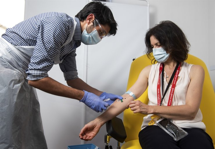 In this handout photo released by the University of Oxford a doctor takes blood samples for use in a coronavirus vaccine trial in Oxford, England, Thursday June 25, 2020. Scientists at Oxford University say their experimental coronavirus vaccine has been shown in an early trial to prompt a protective immune response in hundreds of people who got the shot. In research published Monday July 20, 2020 in the journal Lancet, scientists said that they found their experimental COVID-19 vaccine produced a dual immune response in people aged 18 to 55. British researchers first began testing the vaccine in April in about 1,000 people, half of whom got the experimental vaccine. (John Cairns, University of Oxford via AP)