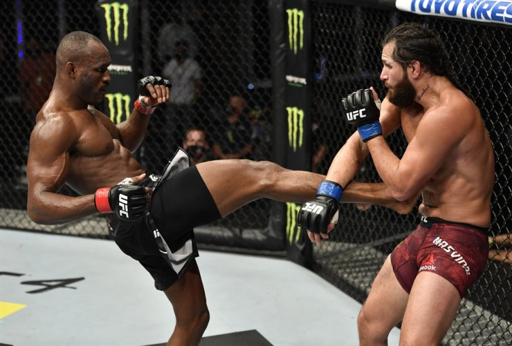 Nigeria's Kamaru Usman, left, kicks Jorge Masvidal in their welterweight championship fight during the UFC 251 event at UFC Fight Island in Abu Dhabi's Yas Island, Sunday. / AFP-Yonhap