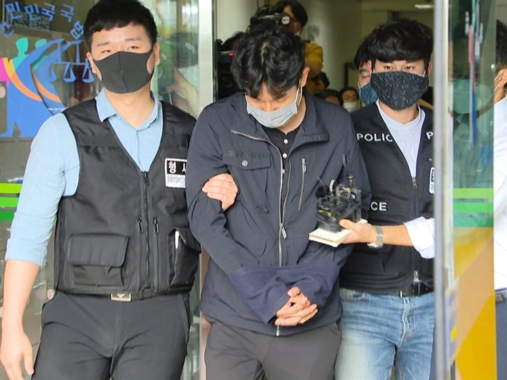 Kim Gyu-bong, head coach of Gyeongju City Hall's semi-pro triathlon club, is taken out of a local court in the southern city of Daegu, Tuesday. / Yonhap