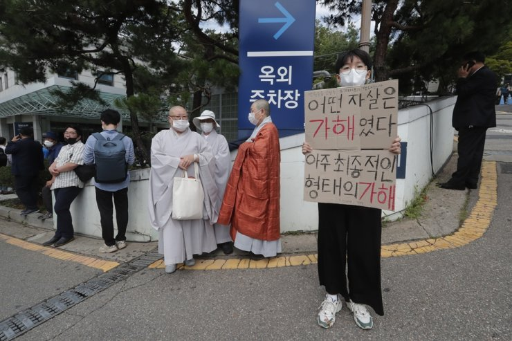 A protester holds a sign at Seoul National University Hospital where a funeral hall for late Seoul Mayor Park Won-soon was established in Seoul, Friday, July 10, 2020. Park left a note saying he felt 'sorry to all people' before he was found dead early Friday. The sign reads 'Some suicides are violence, the ultimate kind of violence.' AP