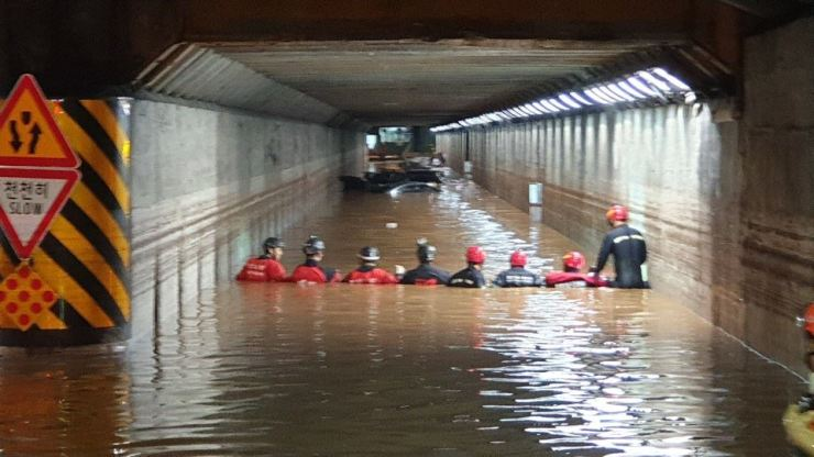 Emergency rescue workers search for people at a flooded underground road tunnel in Busan's Dong-gu District, Thursday. Three people were found dead there. Courtesy of Busan Metropolitan Police Agency