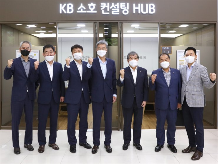 KB Kookmin Bank CEO Hur Yin, center, and Financial Supervisory Service Governor Yoon Suk-heun, third from right, pose with participants in the opening ceremony of the third KB SOHO Mentoring School at the KB SOHO Consulting Hub on Yeouido in Seoul, Thursday. The bank has run the mentoring program since 2016 to support the self-employed who seek to improve the competitiveness of their businesses. / Courtesy of KB Kookmin Bank
