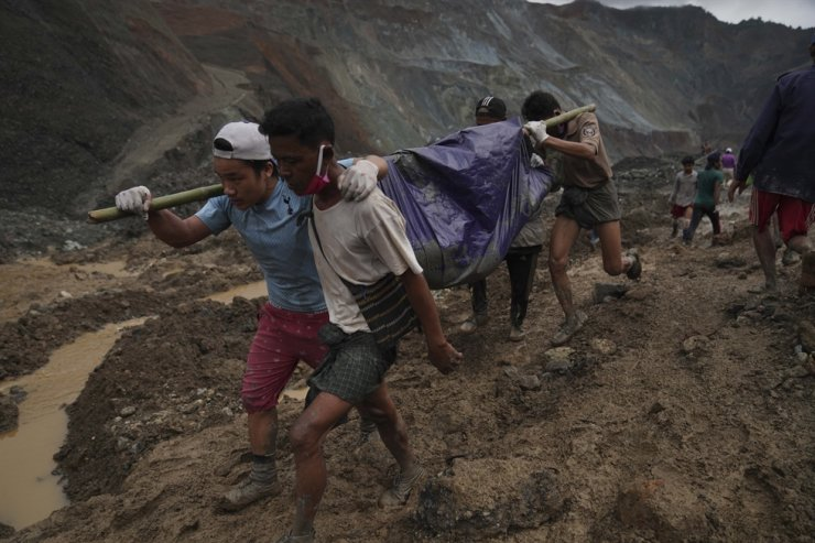Rescue workers use poles to carry a body shrouded in blue and red plastic sheet Thursday, July 2, 2020, in Hpakant, Kachin State, Myanmar. At least 162 people were killed Thursday in a landslide at a jade mine in northern Myanmar, the worst in a series of deadly accidents at such sites in recent years that critics blame on the government's failure to take action against unsafe conditions. AP