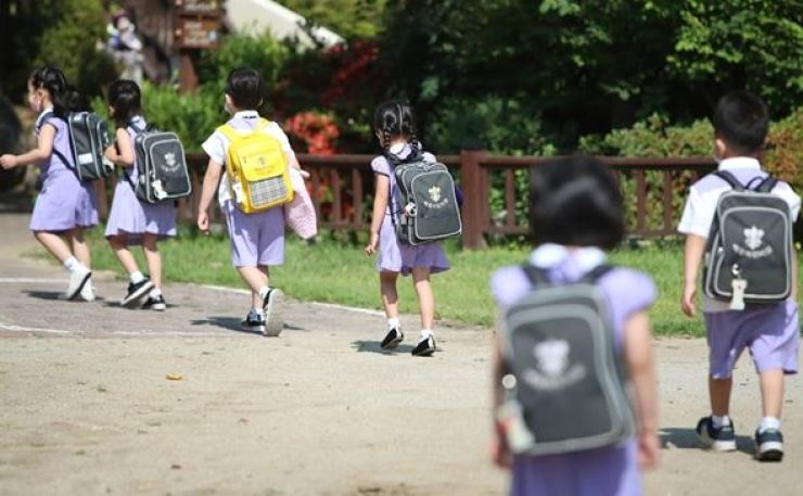 Children enter a kindergarten in Daegu on June 22, maintaining social distancing after the facility reopened following a 122-day shutdown because of the COVID-19 pandemic. Yonhap
