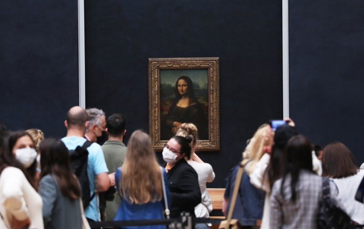 Visitors wearing face masks look at the painting Mona Lisa at the Louvre Museum on its reopening day in Paris, France, July 6, 2020. After three and a half months of closure, the Louvre, one of the most visited museums in the world, reopened on Monday to the public, without lengthy queues of visitors as before the COVID-19 pandemic. /Xinhua