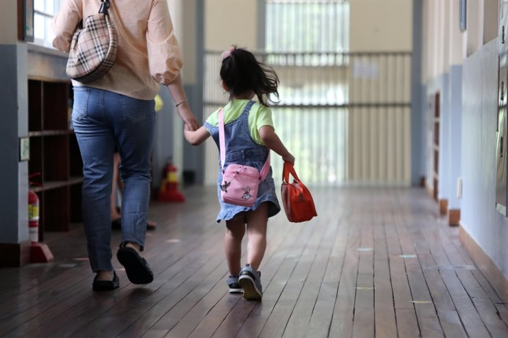 In this July 3, 2019, photo, a girl holding her mother's hand carries her lunch at the Dunsan Elementary School in Daejeon. A recent study says Korea's population will halve by 2100. Korea Times file