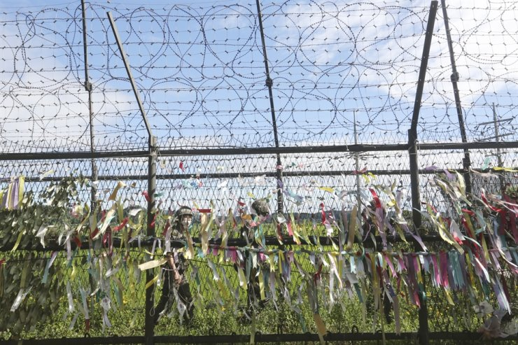South Korean army soldiers wearing face masks to help protect against the spread of the new coronavirus pass by a wire fence decorated with ribbons written with messages wishing for the reunification of the two Koreas at the Imjingak Pavilion in Paju, near the border with North Korea, Sunday, July 26, 2020. AP