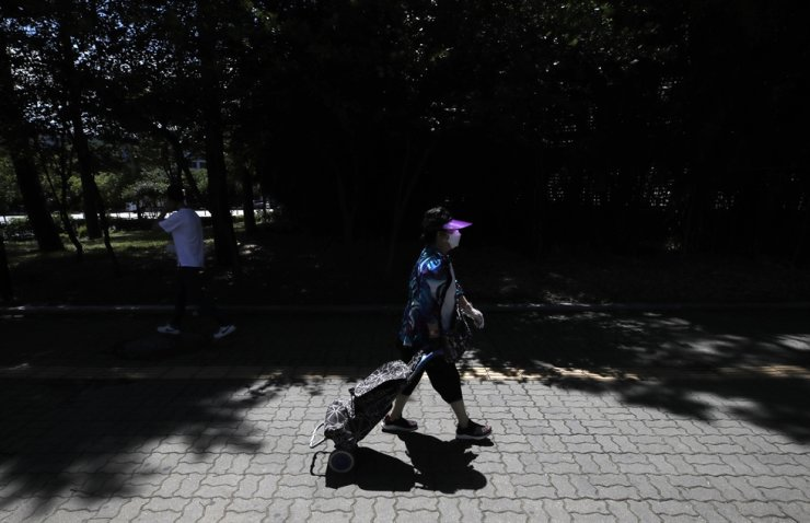 A woman wearing a face mask to help protect against the spread of the new coronavirus pulls her shopping cart in Seoul, Wednesday, July 15, 2020. AP