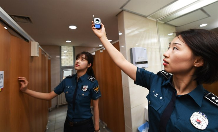 Police officers check for hidden cameras at a public restroom in Anyang, Gyeonggi Province, in this May 30, 2018 file photo. Yonhap
