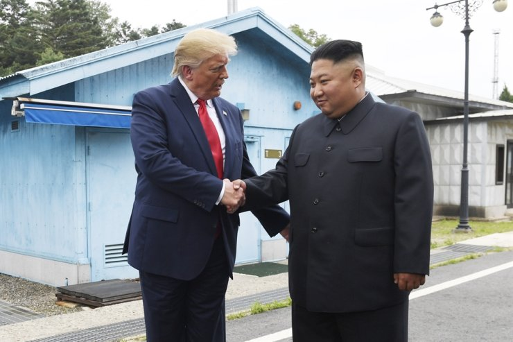 U.S. President Donald Trump and North Korean leader Kim Jong-un shake hands at Panmunjeom in this June 2019 photo. They are not expected to meet each other ahead of the U.S. presidential election in November, according to diplomatic experts. / Korea Times file