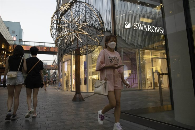 Shoppers pass through an affluent shopping district in Beijing on Tuesday, July 14, 2020. China's economy rebounded from a painful contraction to grow by 3.2% over a year earlier in the latest quarter as anti-virus lockdowns were lifted and factories and stores reopened. /AP