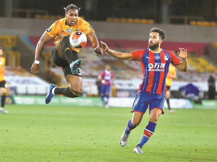 Wolverhampton Wanderers' Adama Traore, left, leaps in the air as he attempts to control the ball as Crystal Palace's Andros Townsend watches during the English Premier League football match between Wolverhampton Wanderers and Crystal Palace at Molineux Stadium in Wolverhampton, England, Monday. / AP-Yonhap