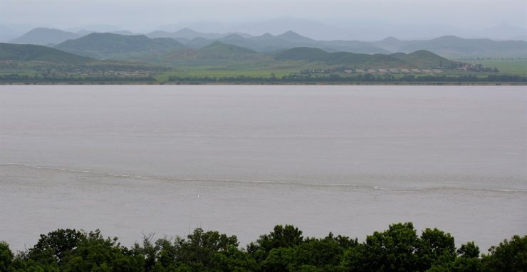 Han River flows between South Korea's Gangwha Island and North Korea's Kaepung, Monday. A North Korean defector is believed to have swam across the border after going through a drain under barbed wire fences to evade South Korean border guards, military officials say. Yonhap