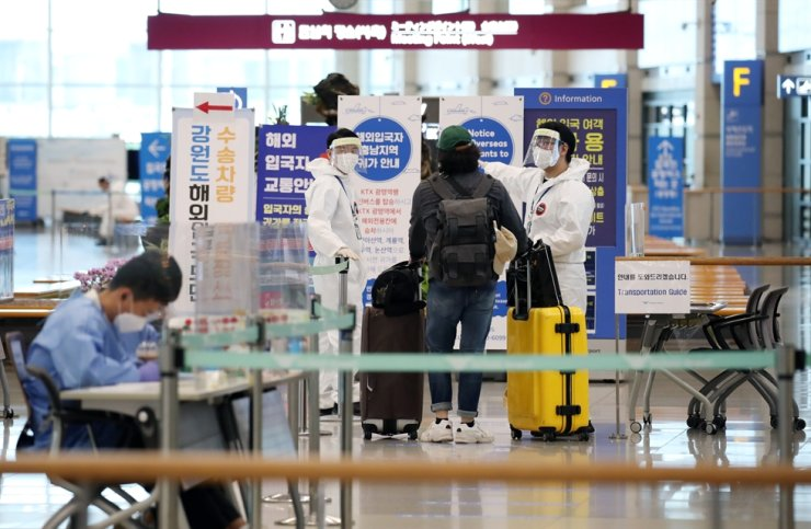 A foreign arrival listens to COVID-19 guidelines from health officials at Incheon International Airport, Wednesday. / Yonhap