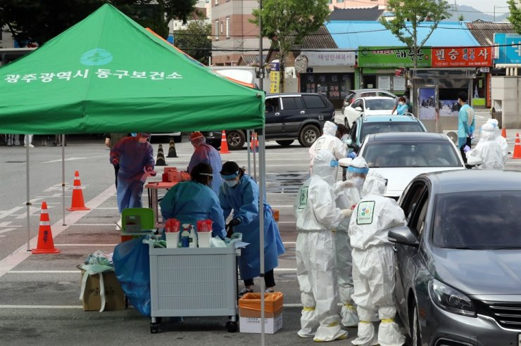 Medical workers test daycare center children and their families at a drive-through center in the southwestern city of Gwangju, Monday, after two children at the center were confirmed to be infected with the virus. Yonhap