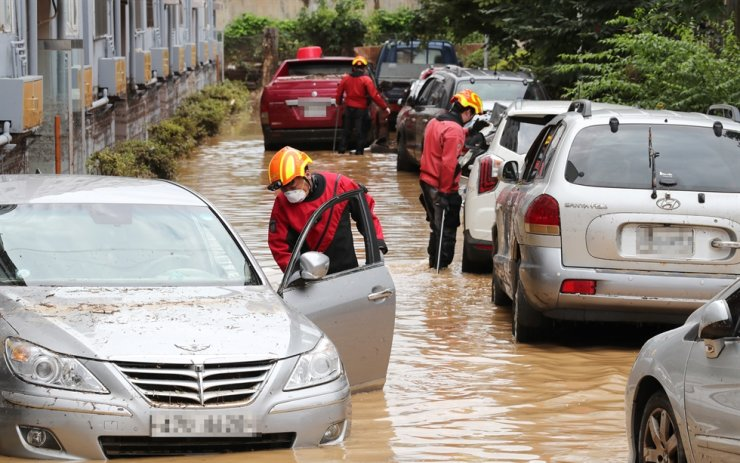Vehicles are half-submerged in a flooded street in Daejeon, Thursday. Yonhap