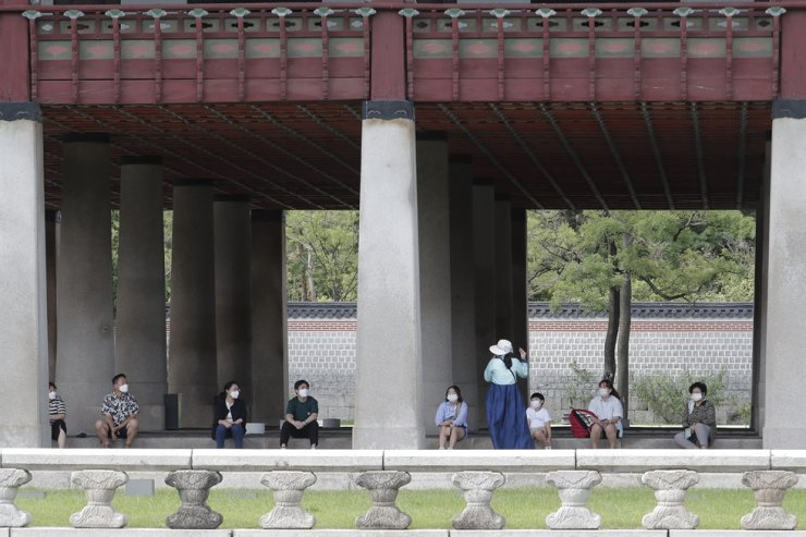 Visitors wearing face masks to help protect against the spread of the new coronavirus sit while maintaining social distancing at the Gyeongbok Palace in Seoul, Saturday, July 25, 2020. AP
