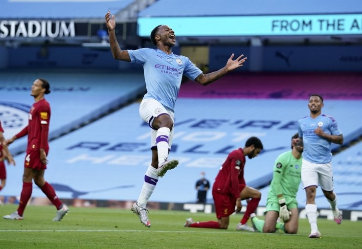 Manchester City's Raheem Sterling, center, celebrates after scoring his team's second goal during the English Premier League football match between Manchester City and Liverpool at Etihad Stadium in Manchester, England, Thursday. / AP-Yonhap