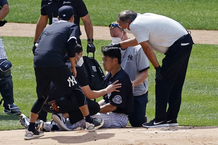 New York Yankees pitcher Masahiro Tanaka is tended to by team medical personnel after being hit by a ball off the bat of teammate Giancarlo Stanton during a baseball a workout at Yankee Stadium in New York, Saturday. AP-Yonhap
