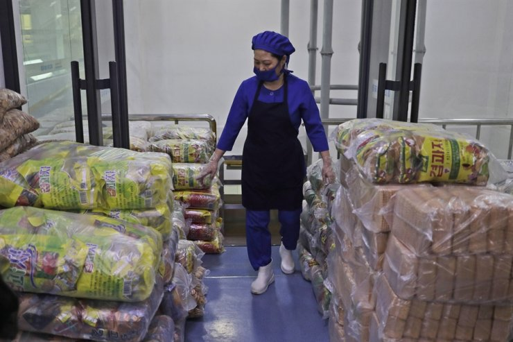 A worker walks among stacks of food at the Kumkhop Trading Co. food factory in Pyongyang, North Korea, in this March 13 photo. AP-Yonhap