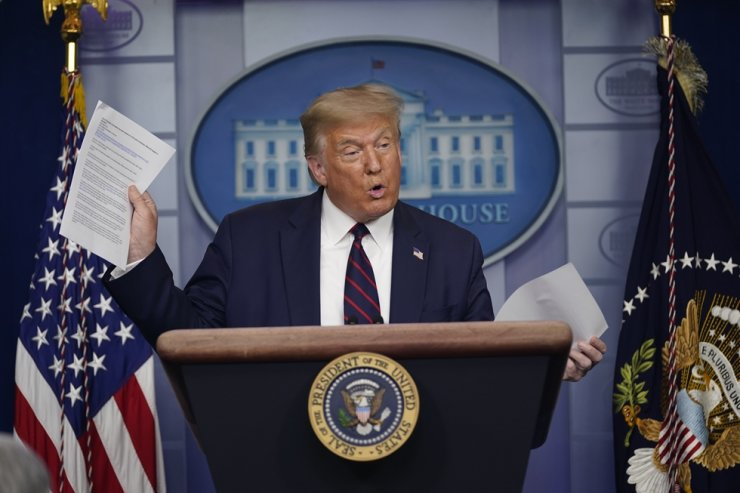 President Donald Trump holds articles as he speaks during a news conference at the White House in Washington, Thursday.    AP-Yonhap