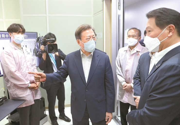 President Moon Jae-in, center, asks SK Group Chairman Chey Tae-won, right, about how the group's chip-making arm SK hynix procures hydrogen fluoride from its local partners during Moon's visit to the company's headquarters in Icheon, Gyeonggi Province, Thursday. / Yonhap