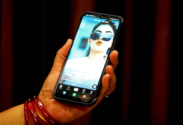 A woman watches a short video on the Chinese video-sharing app TikTok on her smartphone, in Bhopal, central India, 29 June 2020. /EPA