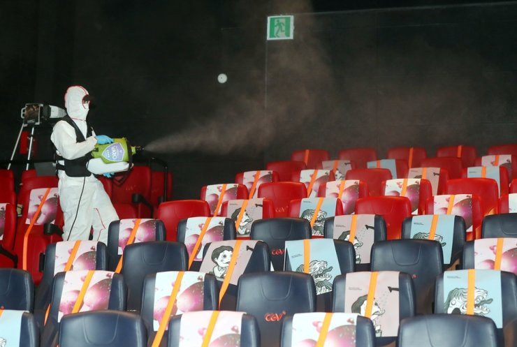 A health worker disinfects seats in a theater in Bucheon, Gyeonggi Province, Tuesday. The 24th Bucheon International Fantastic Film Festival ended Thursday. Yonhap