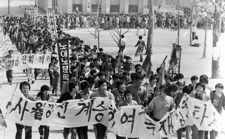 This photo from the 1980s shows university students launching an anti-government protest. The banner reads 'Bring the dictatorship down with the defiant spirit of the April protests.' / Korea Times file