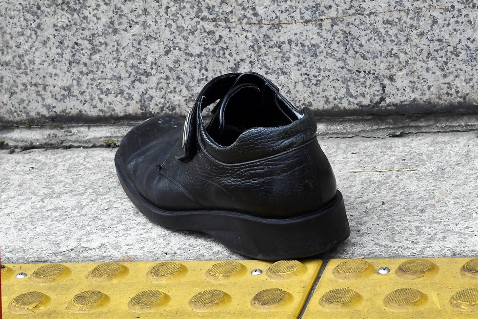 Jung Chang-ok, a protester who threw his shoe at President Moon Jae-in last week in the National Assembly, speaks during an outdoor news conference in front of Dong Hwa Duty Free Shop in central Seoul, Monday, with his shoe on the table. Some right-wingers lauded him as a man of courage. / Yonhap