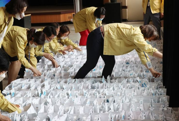 Public officials prepare kits packed with quarantine-related goods, including face masks and thermometers, in the southwestern city of Gwangju, Tuesday, for delivery to people who are self-quarantining at home. Yonhap