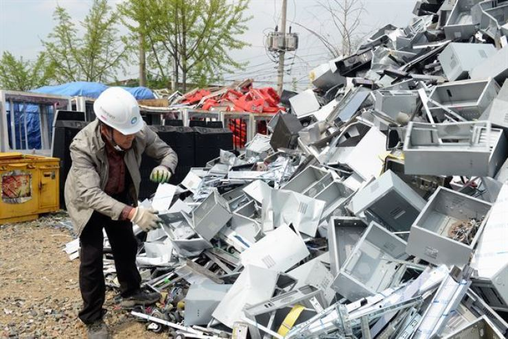 A Korea Environment Corporation official examines metal scrap from computer parts at a recycling firm in Yangju, Gyeonggi Province. Courtesy of Korea Environment Corporation