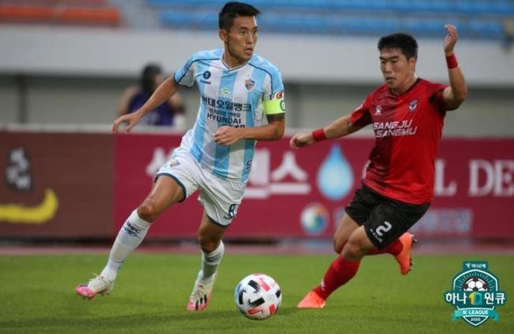Ulsan Hyundai FC captain Shin Jin-ho, left, dribbles past Sangju Sangmu's defender Bae Jae-woo during the K League 1 13th round match at the Sangju Citizen's Stadium, Saturday. / Courtesy of K League