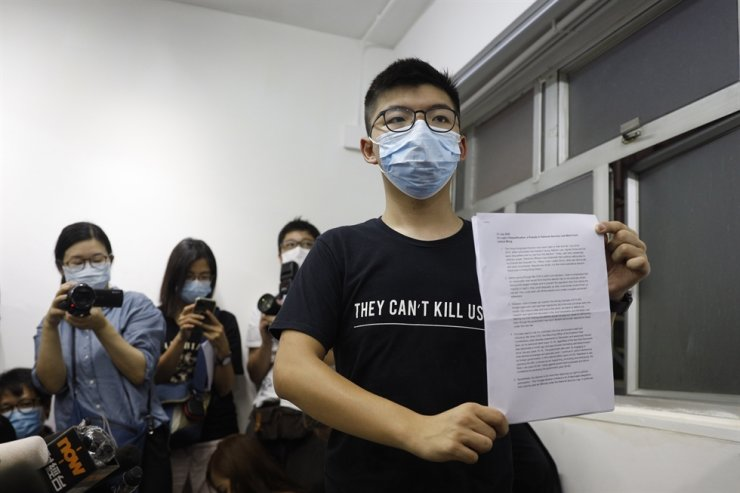 Hong Kong pro-democracy activist Joshua Wong shows his disqualification notice during a press conference in Hong Kong, Friday. On Thursday, 12 pro-democracy candidates including prominent pro-democracy activist Joshua Wong were disqualified from running in the legislative elections, as they were deemed to not comply with the Basic Law or pledge allegiance to the city and Beijing. / AP-Yonhap