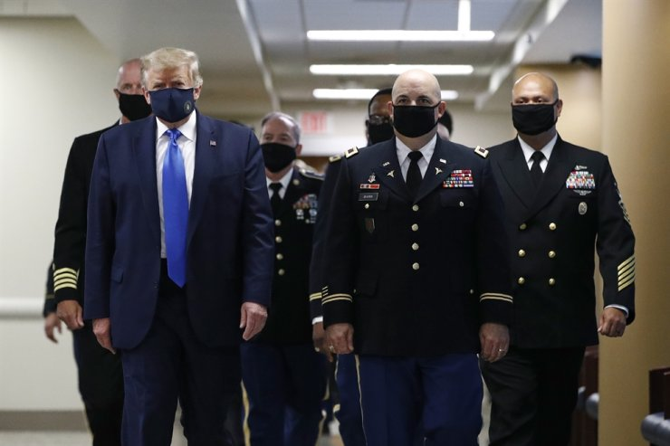 U.S. President Donald Trump, foreground left, wears a face mask as he walks with others down a hallway during a visit to Walter Reed National Military Medical Center in Bethesda, Md., July 11. AP