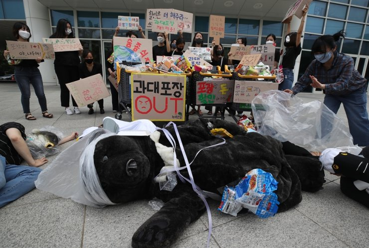 Members of environmental groups perform a skit in front of Emart in Seoul's Seongdong-gu District, July 2, demanding the store immediately introduce a ban on product repackaging. Yonhap