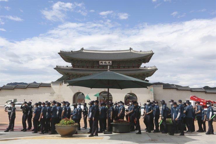 Police offices wearing face masks to help protect against the spread of the new coronavirus wait to cross a road in front of the Gyeongbok Palace in Seoul, Saturday, July 25, 2020. AP