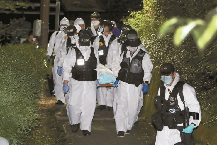 Policemen carry the body of Park Won-soon who was found dead in northern Seoul early Friday. / Yonhap