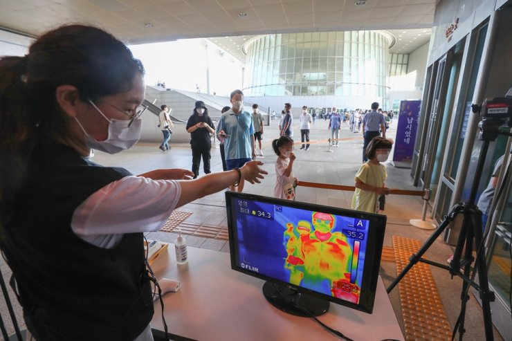 A National Museum of Korea official carries out temperature checks of visitors, Sunday, as a precaution to help slow the spread of COVID-19. The museum in Seoul reopened last Wednesday. / Yonhap