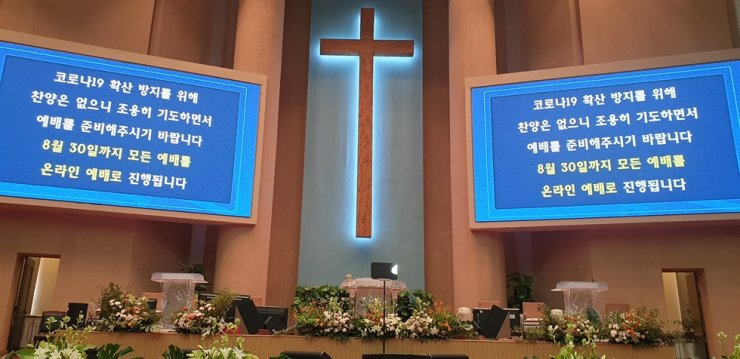 Two screens set up on both sides of the cross at Yoido Full Gospel Church in Seoul on Sunday read online church services will be continued until Aug. 30. / Yonhap