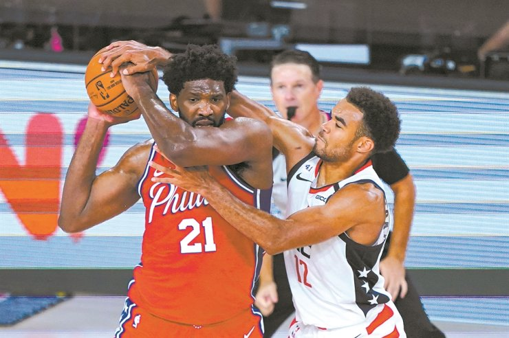 Washington Wizards guard Jerome Robinson, right, tries to tie up Philadelphia 76ers center Joel Embiid during the second half of an NBA basketball game Wednesday in Lake Buena Vista, Fla. / AP-Yonhap