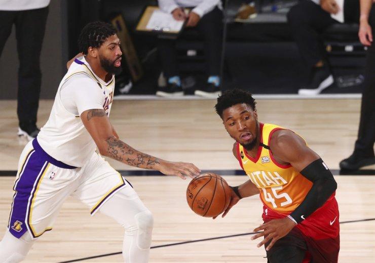 Utah Jazz guard Donovan Mitchell, right, controls the ball near Los Angeles Lakers forward Anthony Davis during the second half of an NBA basketball game Monday in Lake Buena Vista, Fla. / AP-Yonhap