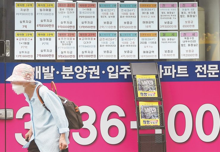 A woman walks past a list of offerings of rent and sales of apartments put up on the entrance of a real estate agent's office in Seoul. Korea Times file