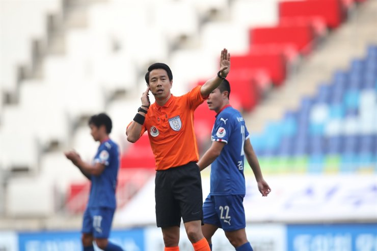 K League referee Kim Yong-yoo, center, talks to video assistant referees during the K League second-round match between Suwon Samsung and Ulsan Hyundai at Suwon World Cup Stadium, May 17. / Courtesy of Korea Football Association