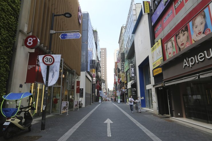 A couple wearing face masks to help protect against the spread of the coronavirus walks along on a nearly empty shopping street in Seoul, Sunday, Aug. 23, 2020. AP